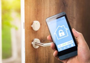 Man uses his smartphone with smarthome security app to unlock the door of his house.
