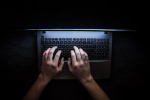Man typing on Laptop in a dark room.