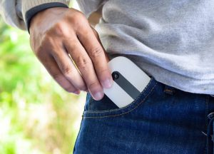 Man's hand put a pocket wifi in his jeans pocket.Modem wireless internet accessory