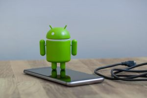 Google Android figure standing on a smart phone (1)