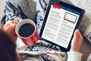 Woman reading news on tablet with cup of coffee. Online education concept