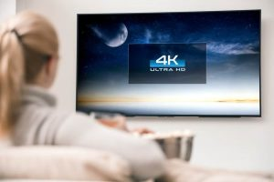 Woman watches tv with 4k ultra hd resolution.