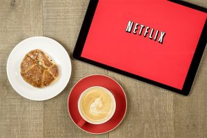 An image featuring a tablet that has Netflix opened with food and coffee next to the tablet