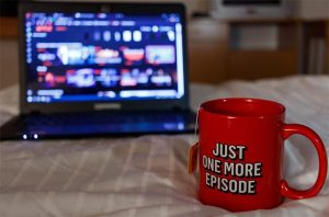 """An image featuring a cup that says """"just one more episode"""" with Netflix opened in the background"""