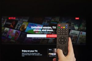 An image featuring a person holding a TV remote and searching on Netflix