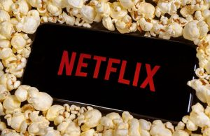 An image featuring a phone that has Netflix opened and the phone is on top of popcorn