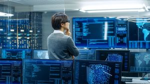 An image featuring a person standing in a server/control room representing internet activity concept
