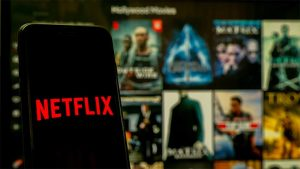An image featuring a phone that has the Netflix logo on it with multiple TV movies and shows from Netflix in the background