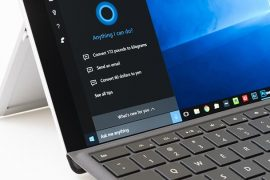 An image featuring a laptop with Cortana opened on the screen